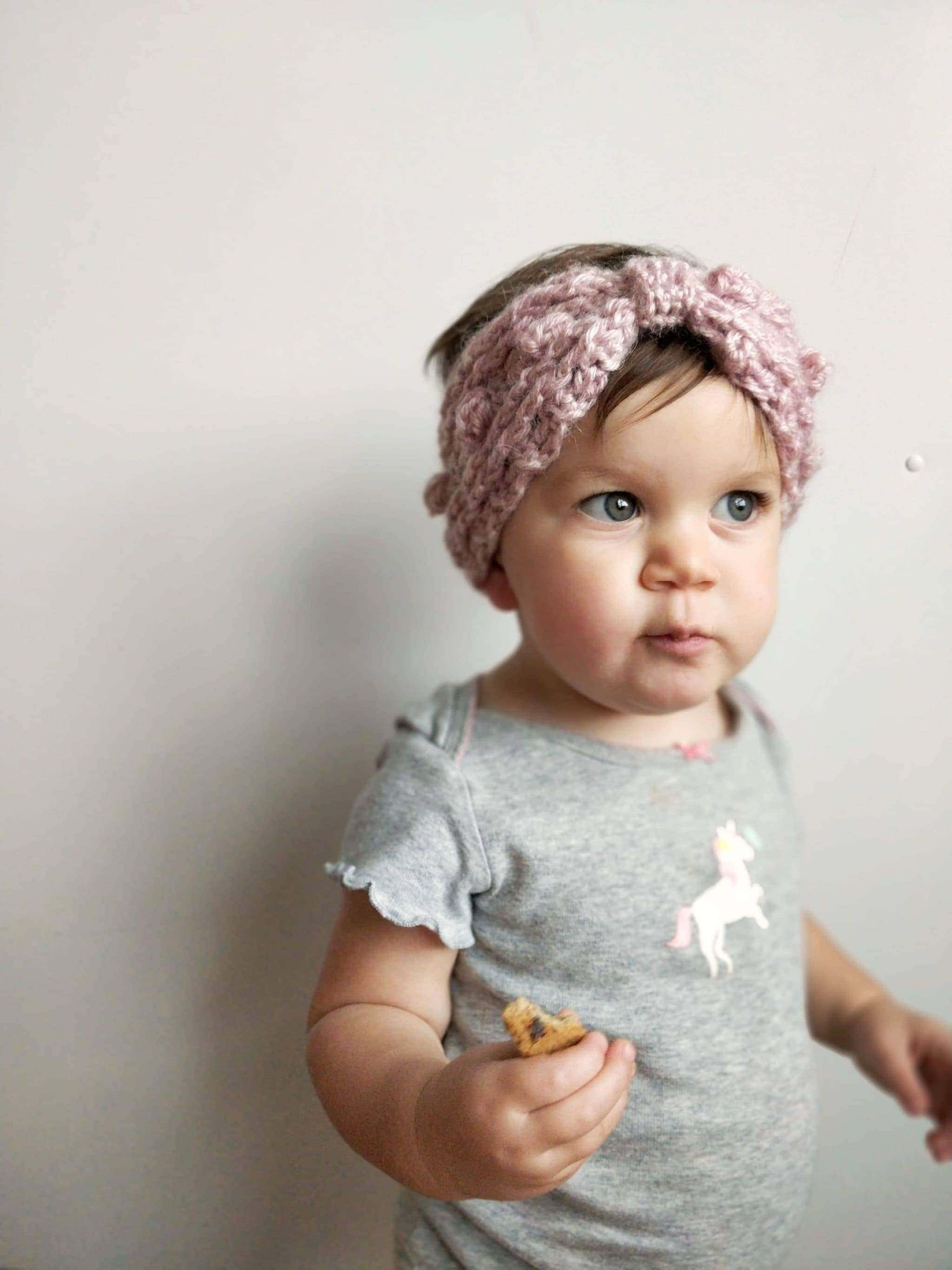 Little girl with colored eyes wearing the Victoria Ear Warmer and holding a cookie