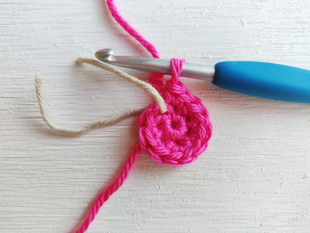 Bright pink yarn with a cream colored yarn stitch marker and silver crochet hook