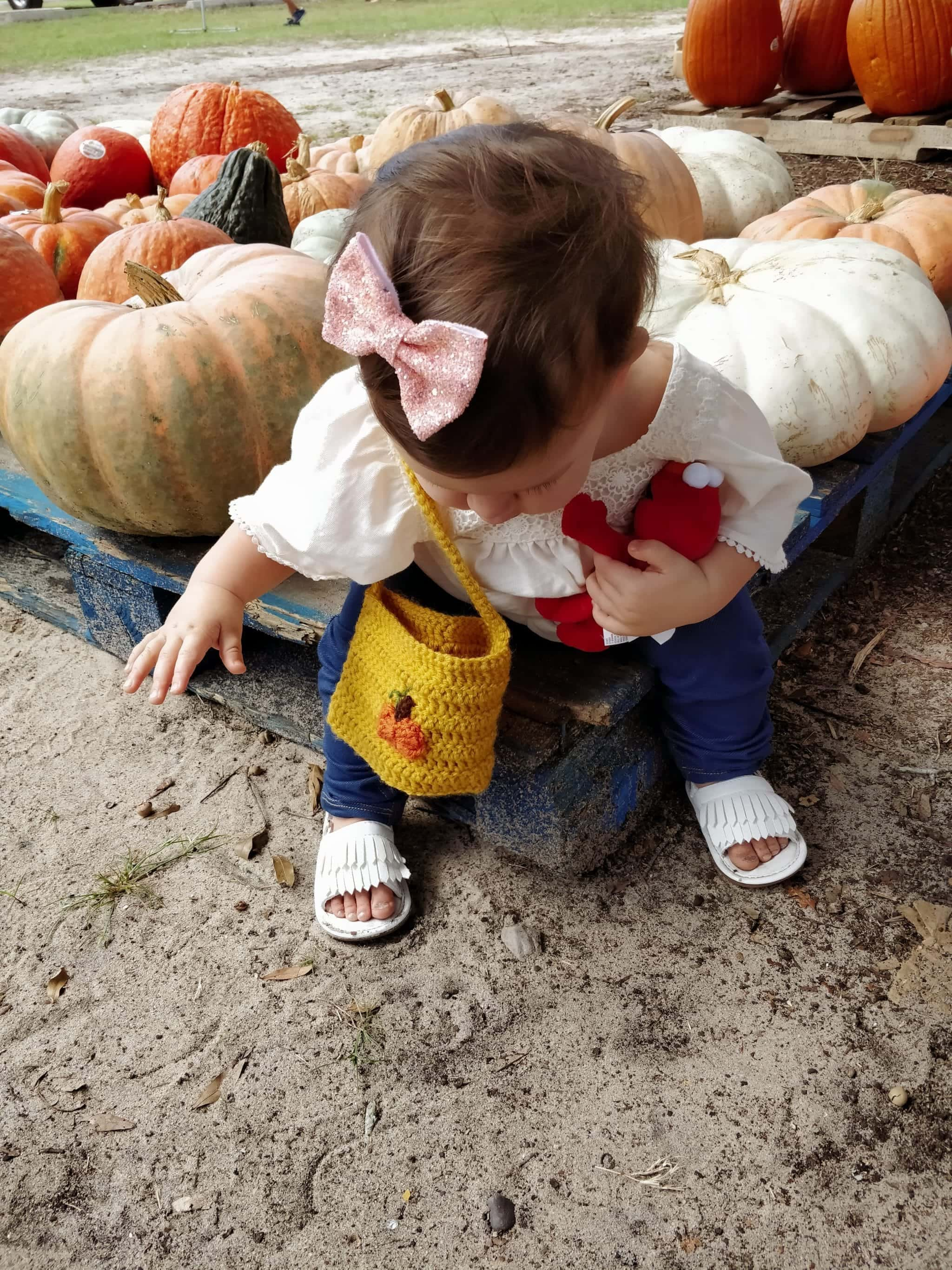 Toddler wearing a yellow handbag while sitting down at a pumpkin patch