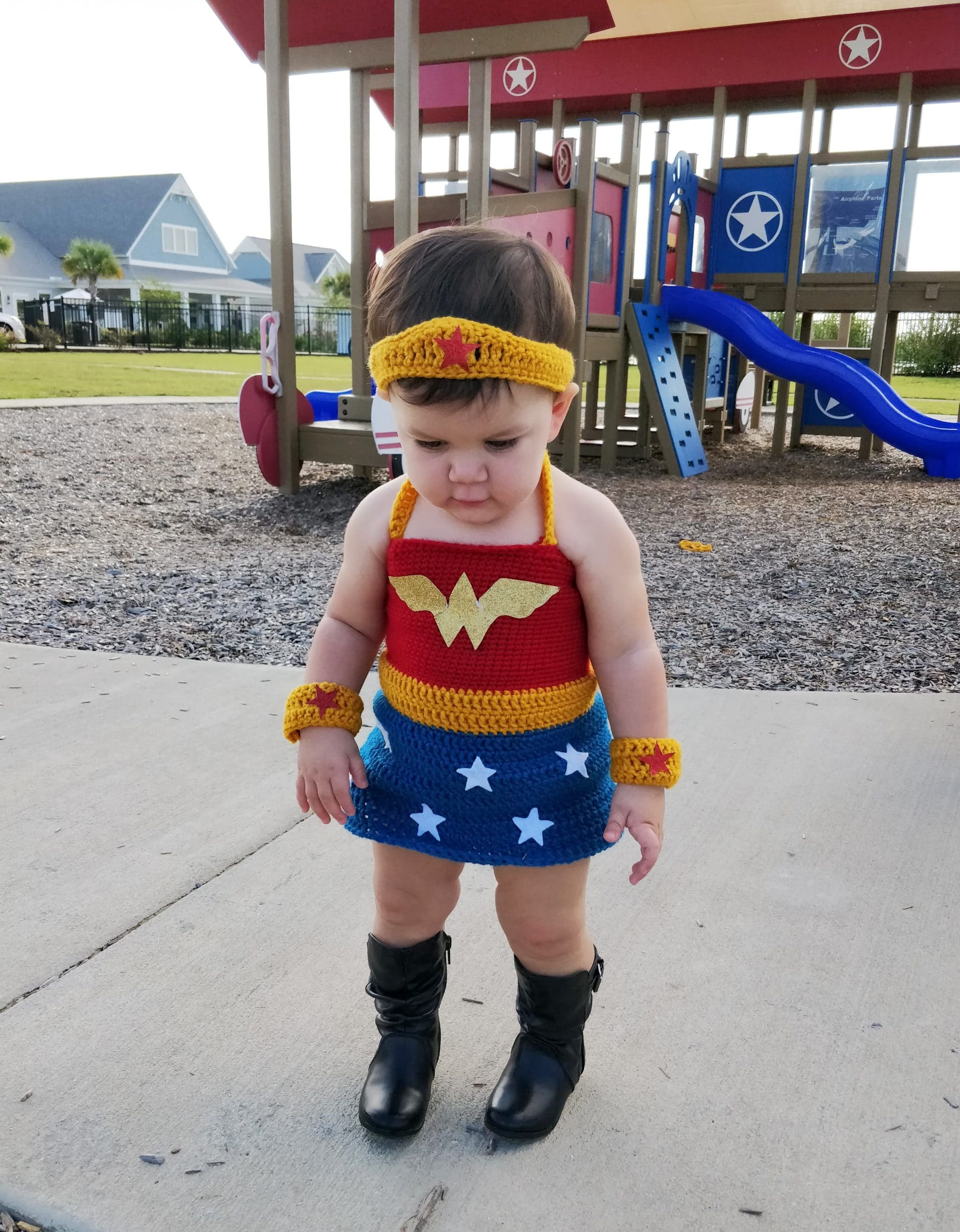 Little girl in black boots wearing wonder woman crochet outfit at the playground
