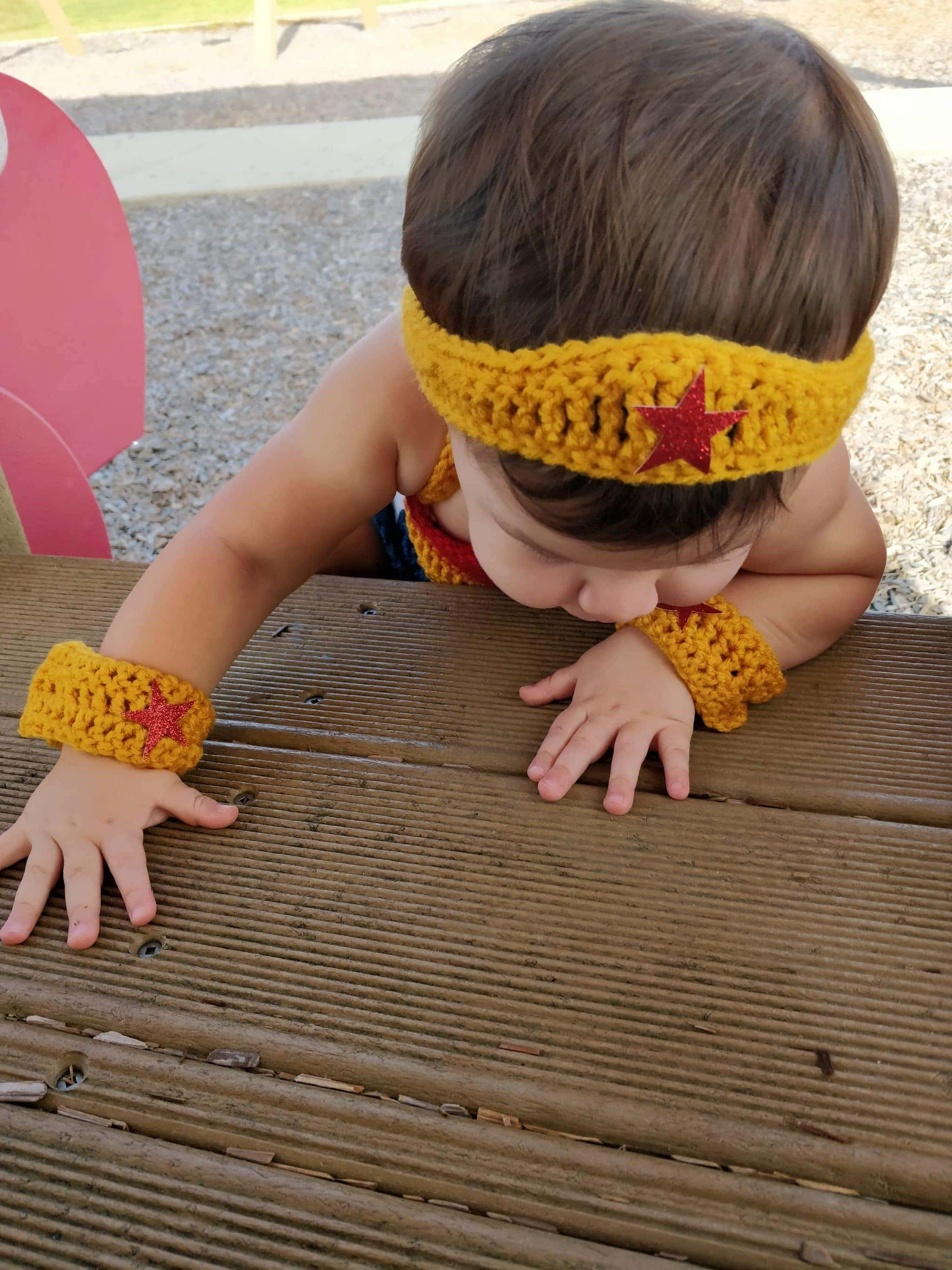 Crochet headband and cuff links of wonder woman outfit being worn by little girl at the park