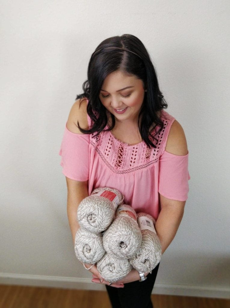 Woman wearing a pink shirt holding 5 skeins of yarn in her arms