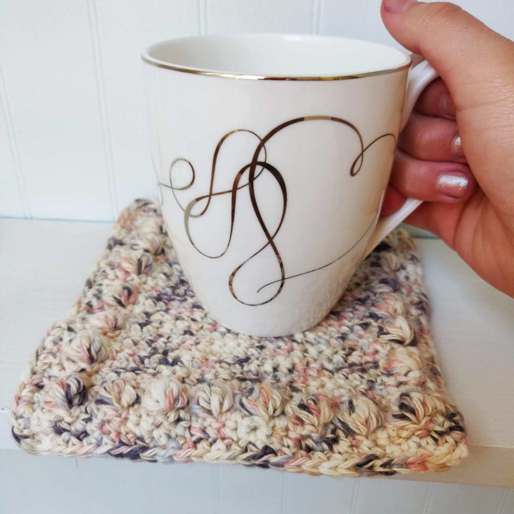 Crochet bobble coaster with fine china coffee mug embossed with golden heart shaped patterns