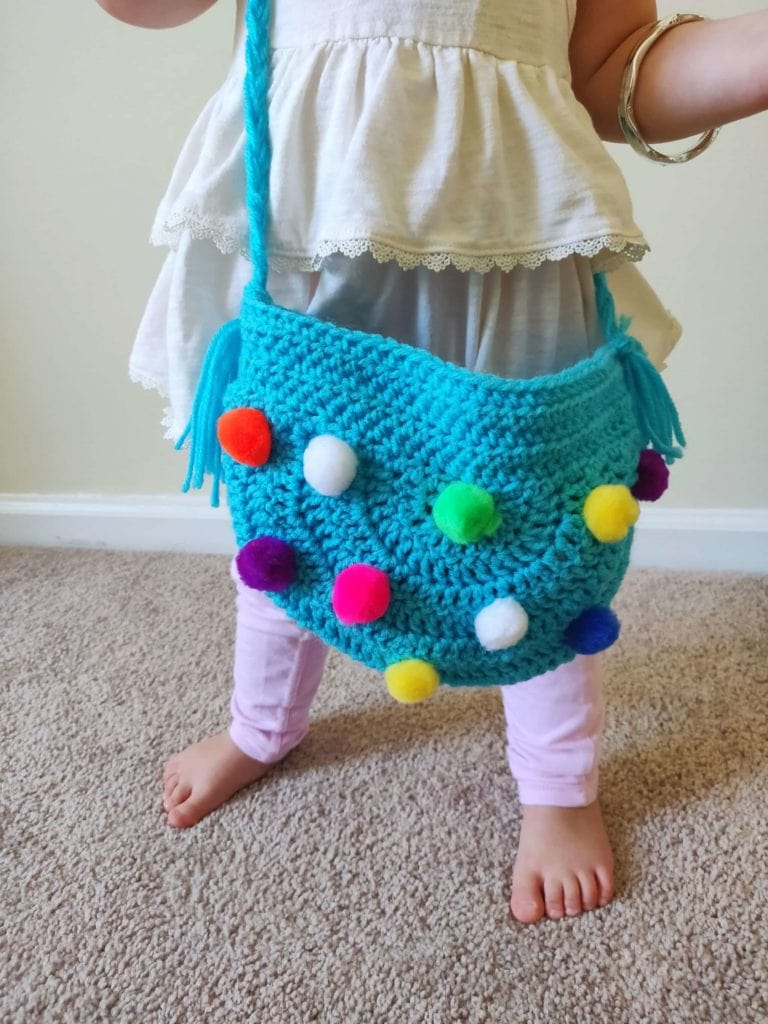 Little girl wearing handmade crochet bag in teal color with pom-poms adorning the sides