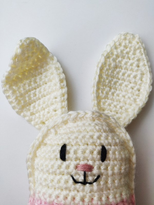 Close up of crochet bunny doll face with pink nose and black eyes and mouth