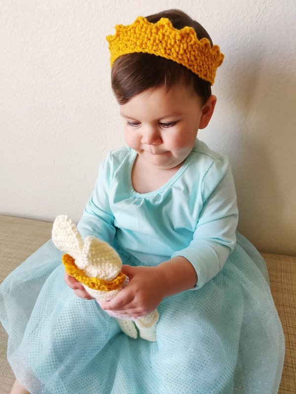 Little girl playing with her crochet bunny doll while wearing a matching princess crown in gold
