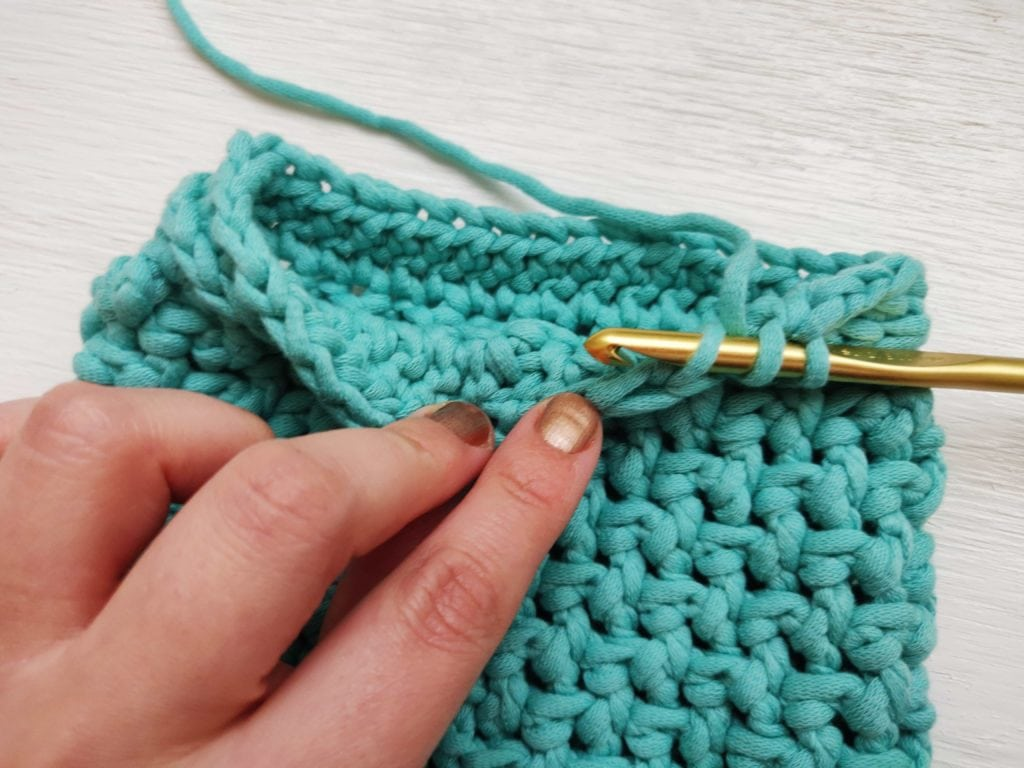 Close up of a crochet stitch through teal yarn with a golden crochet hook