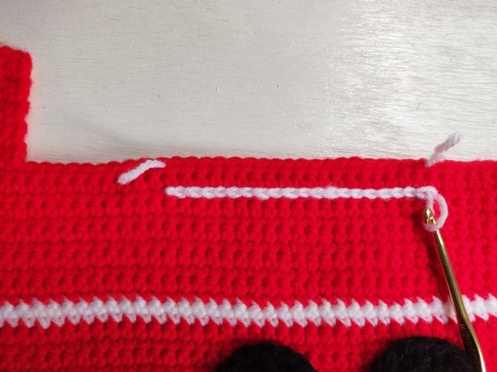 Stitching the fire hose onto the fire truck with different colored yarn