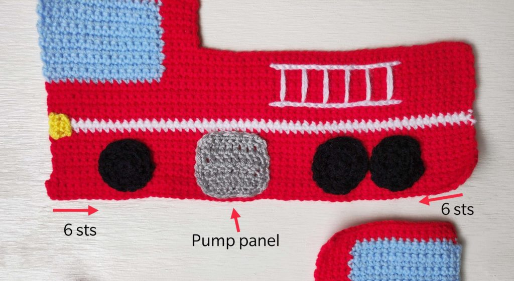 Crochet fire truck plush laying flat showing pump panel and wheels on one side