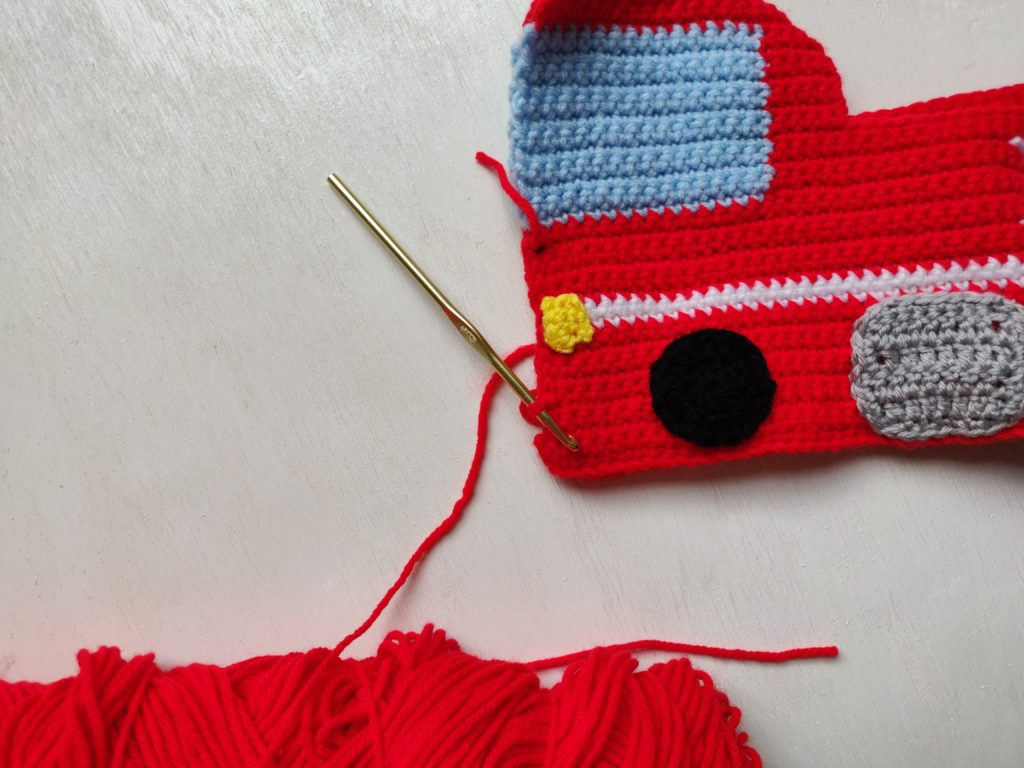 The wheels and lights going onto the red fire truck crochet plush