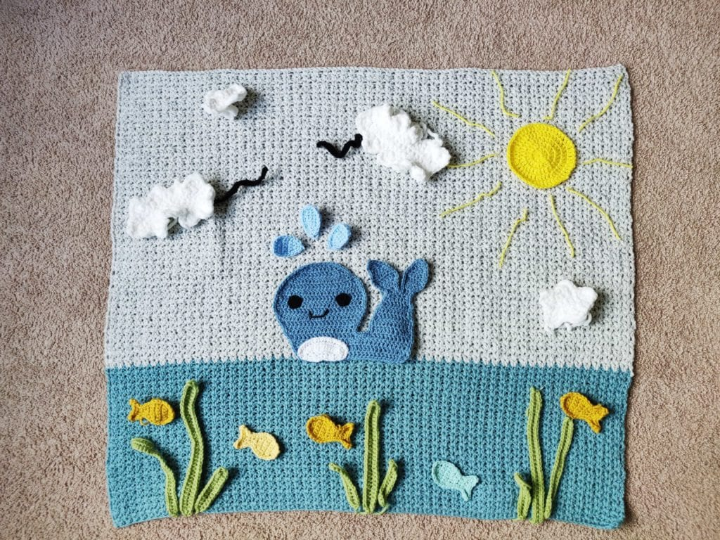 Crochet whale baby blanket laying on the ground