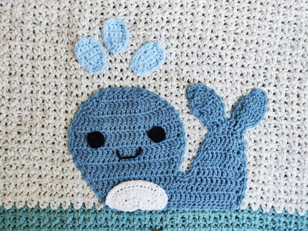 Crochet whale applique attached to blanket with black eyes and mouth, white belly, and light blue water spraying from blowhole