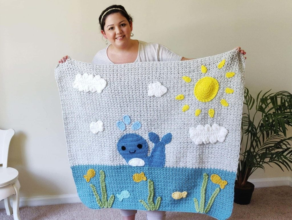 Finished crochet baby blanket with whale, sun, clouds, fish, and seaweeds