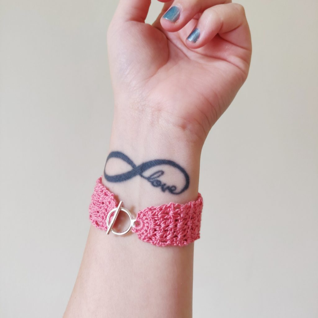 Closeup of pink bracelet on woman's arm with tattoo saying love in infinity symbol