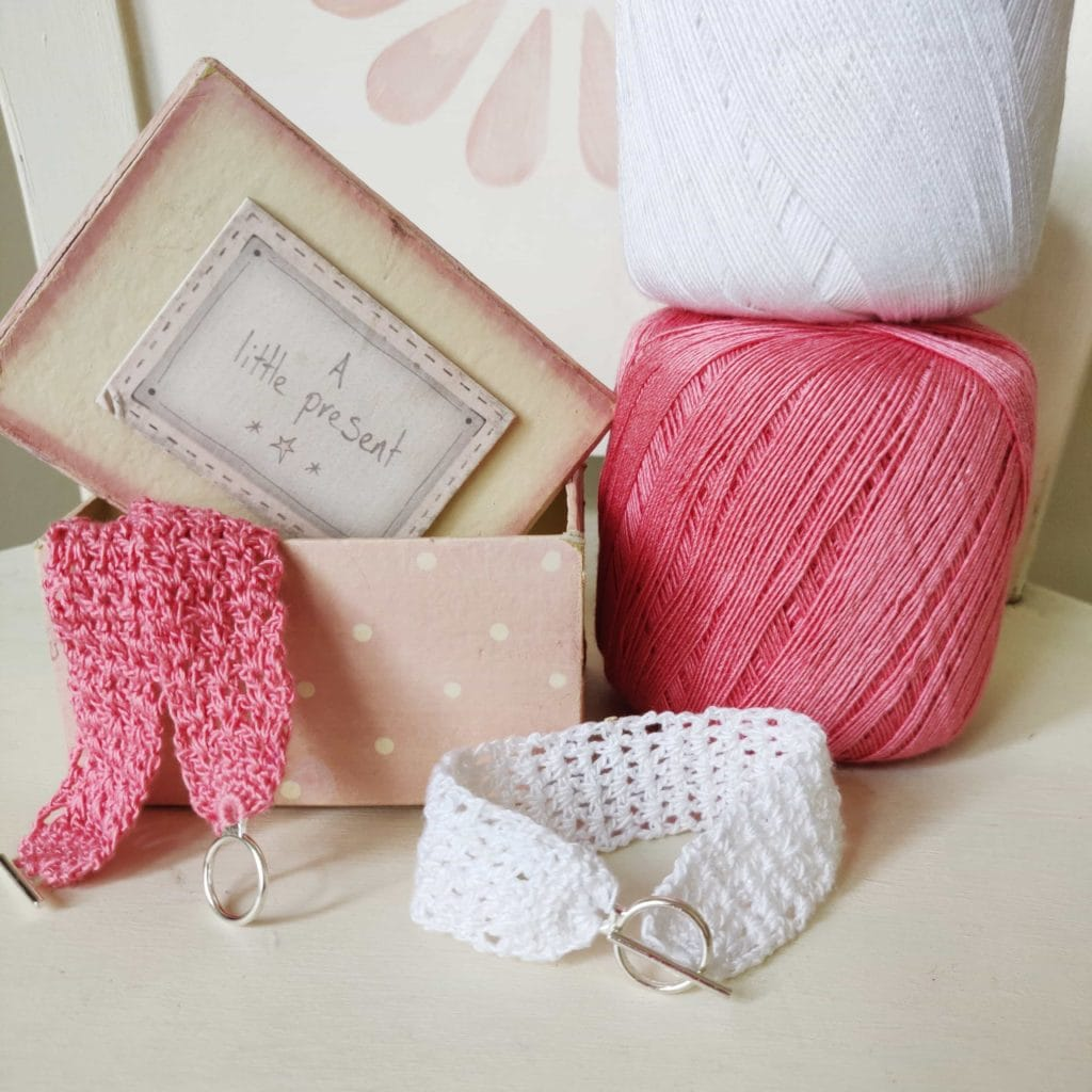 Pink and white yarn next to a box with two handmade fiber bracelets