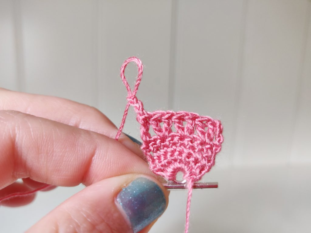 Vibrant pink crochet stitches on metal eyelet attached to wooden rod serving as makeshift bracelet latch