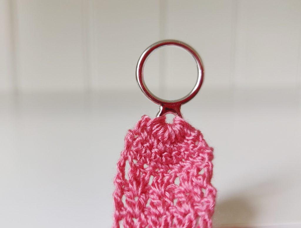 Round metal circle with pink fibers hanging from it