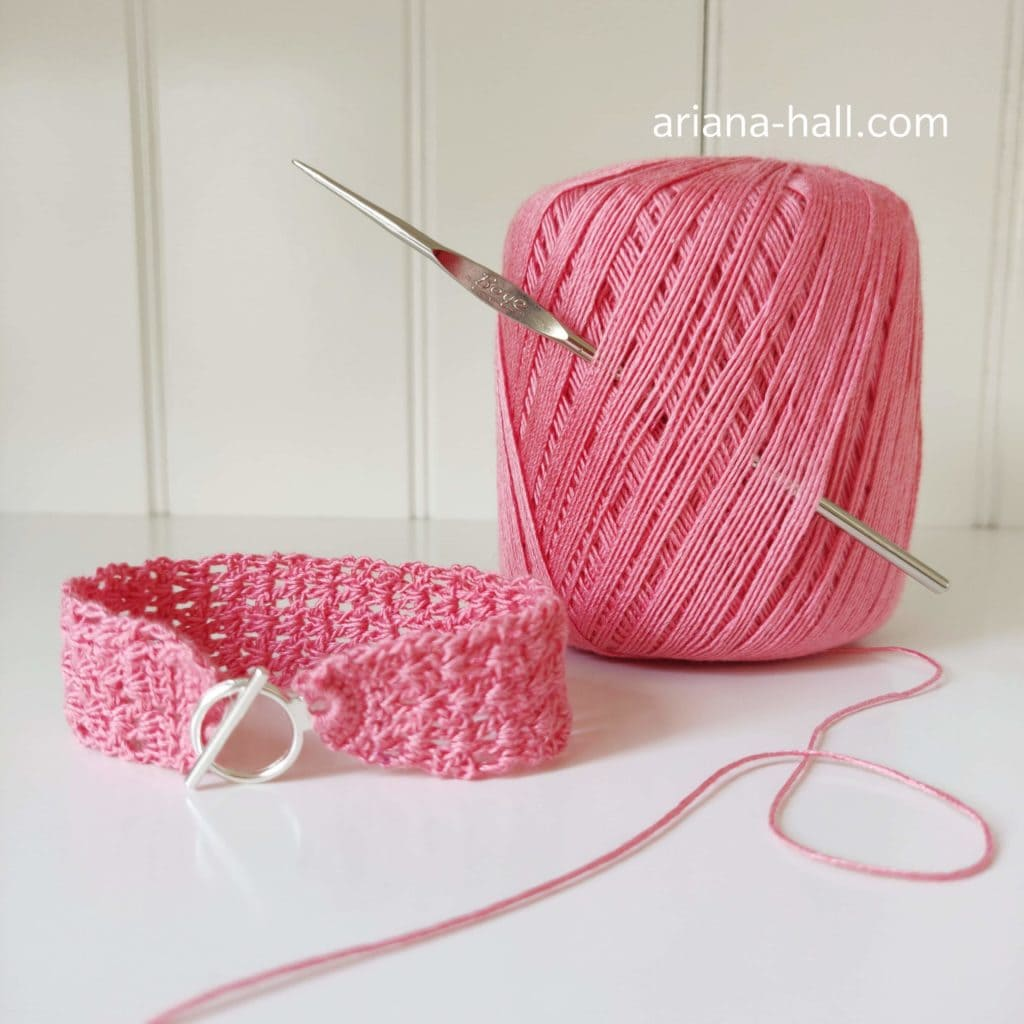Completed Aria Bracelet handmade crochet project with pink yarn and golden hook in background