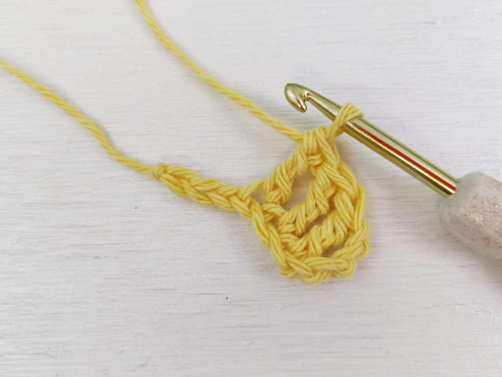 Gold chrome crochet hook and yellow yarn stitches