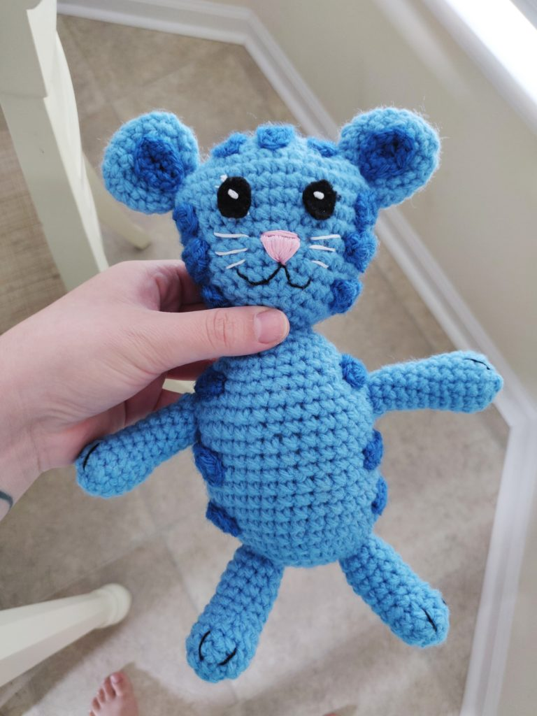 Finished Tigey the tiger crochet doll pattern in bright blue