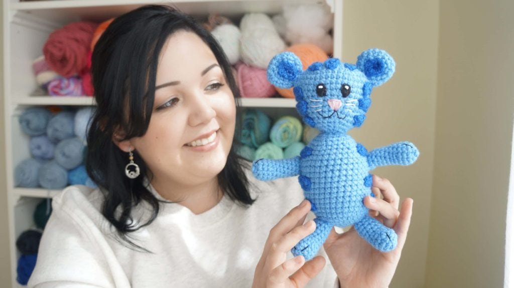 Completed Tigey the crochet tiger doll being held up by smiling Ariana Hall with yarn stash in the background