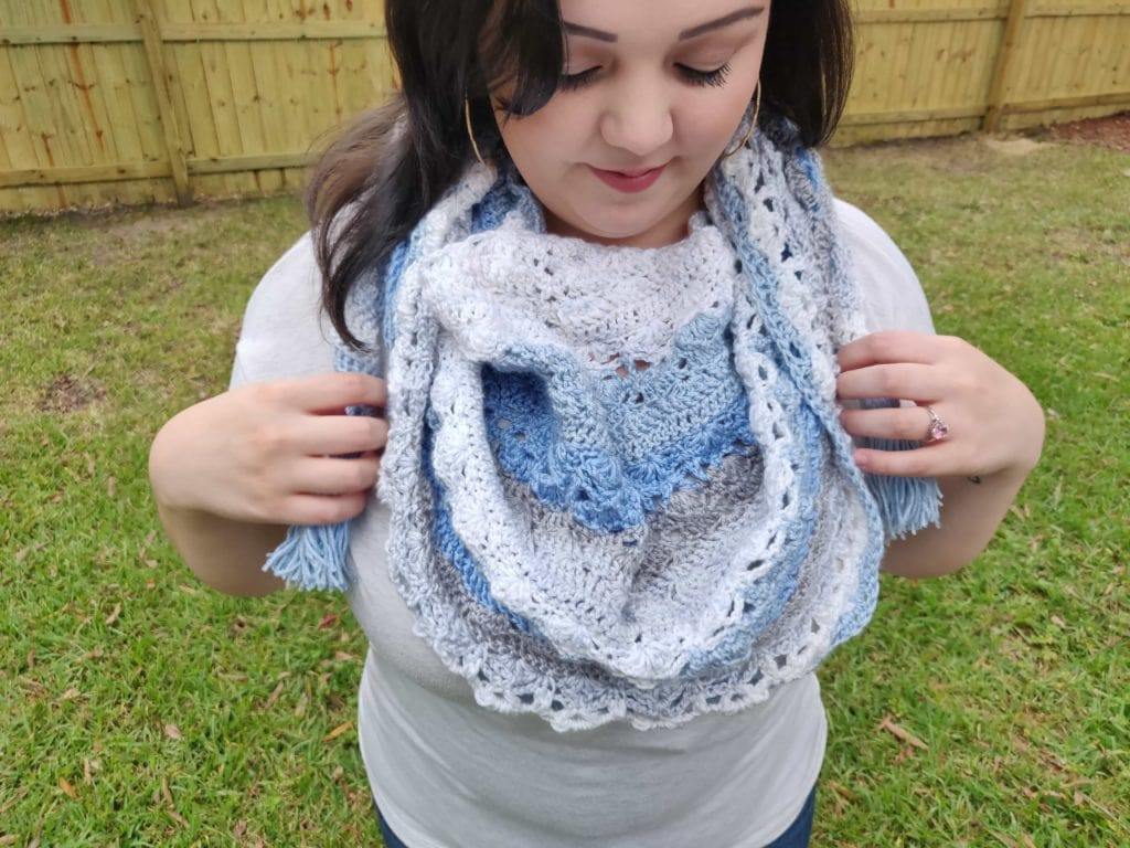 Close up of completed crochet shawl pattern in blue, light blue, and white yarn