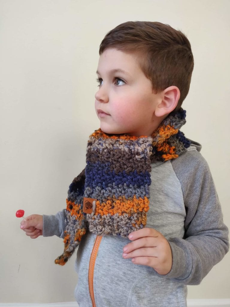 Small boy with brown hair wearing finished kids scarf and holding a red lollipop