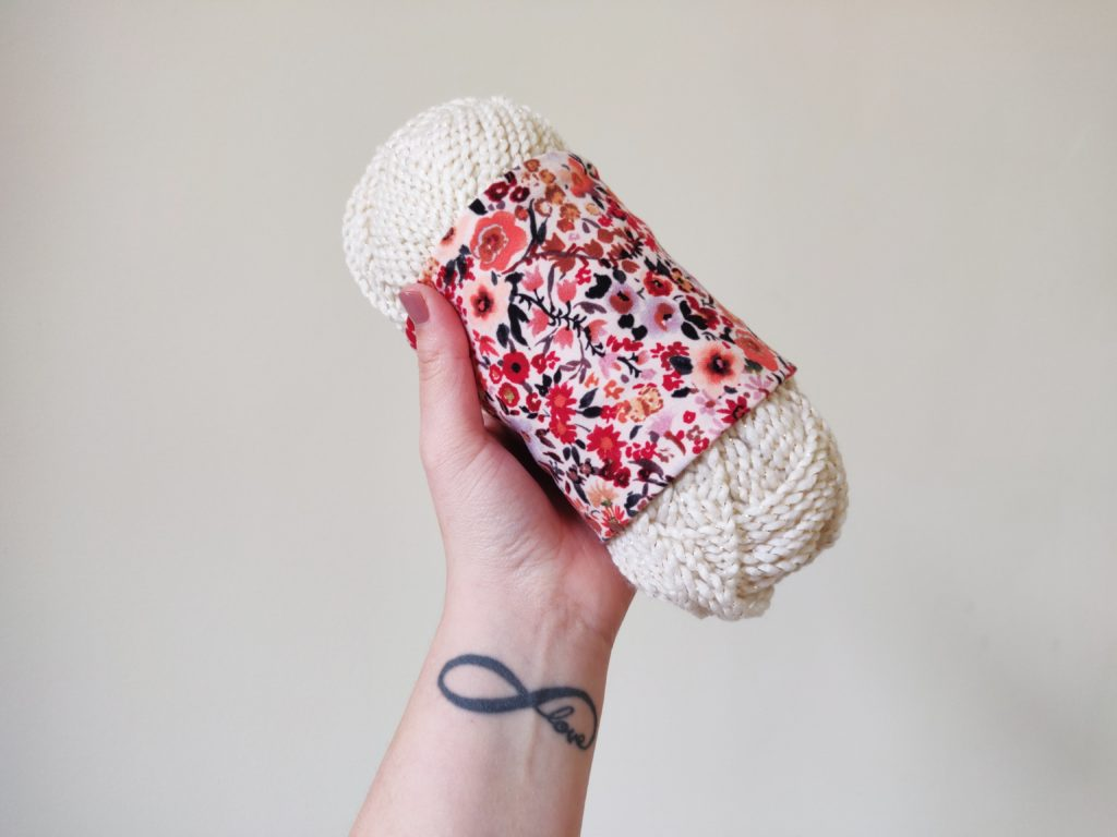 A skein of white cotton yarn wrapped in sewn fabric yarn holder