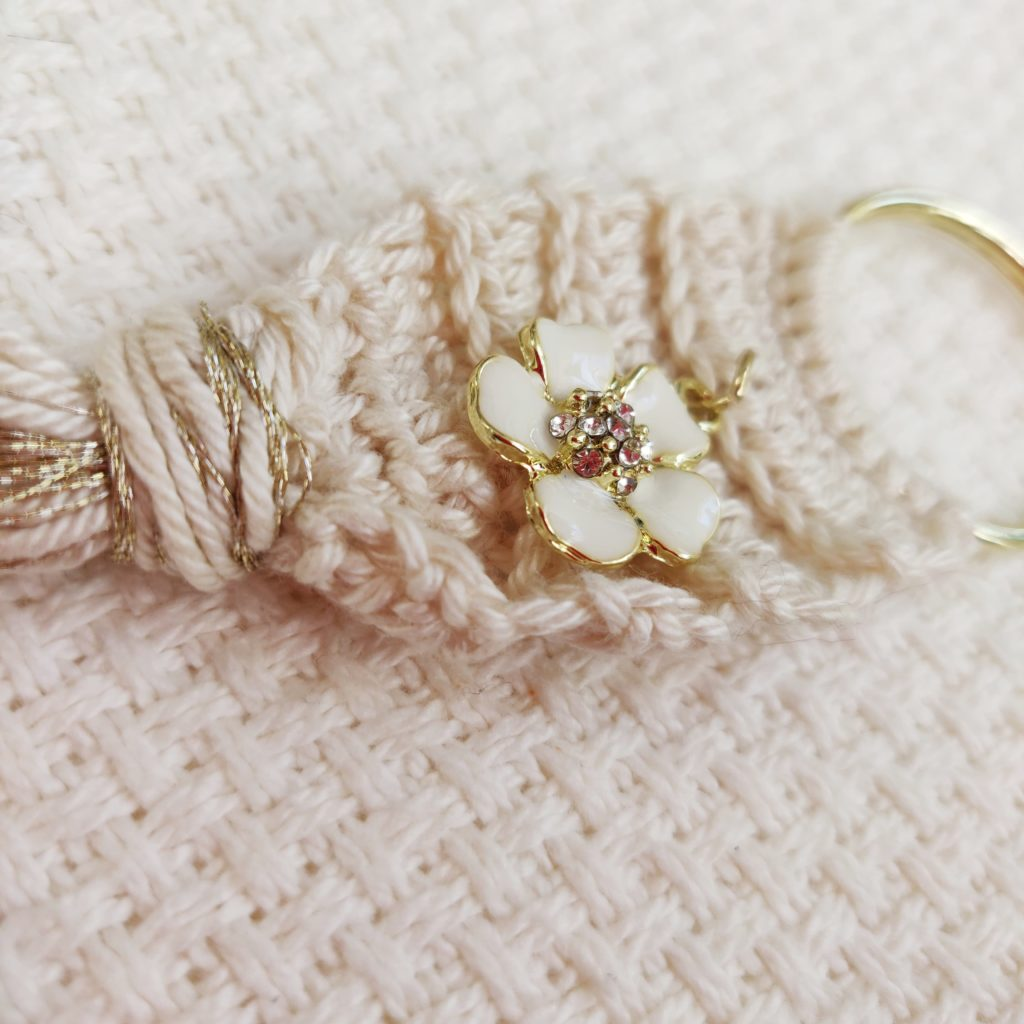 Close up of white metal flower embellishment on crochet key chain with a white woven background