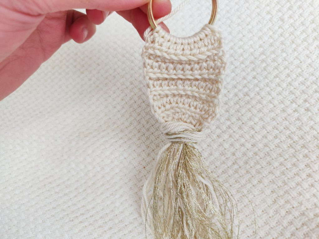 Accent white and gold yarn tied around crochet yarn key chain