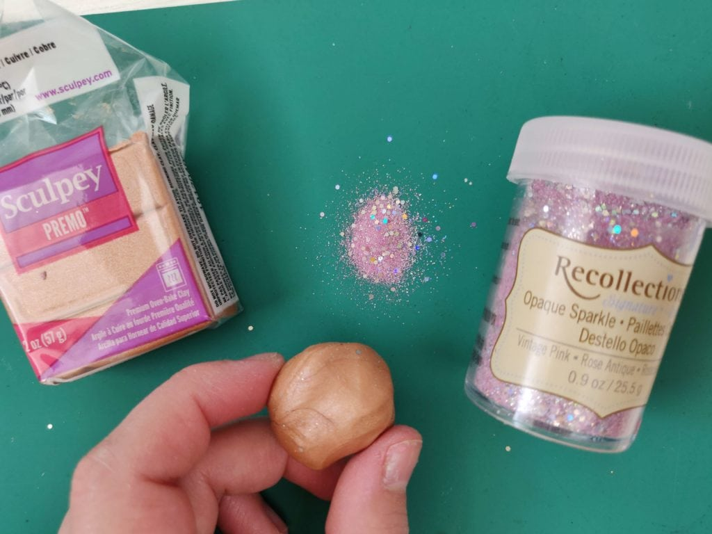 Polymer clay ball ready to be rolled in a pile of pink sparkle glitter