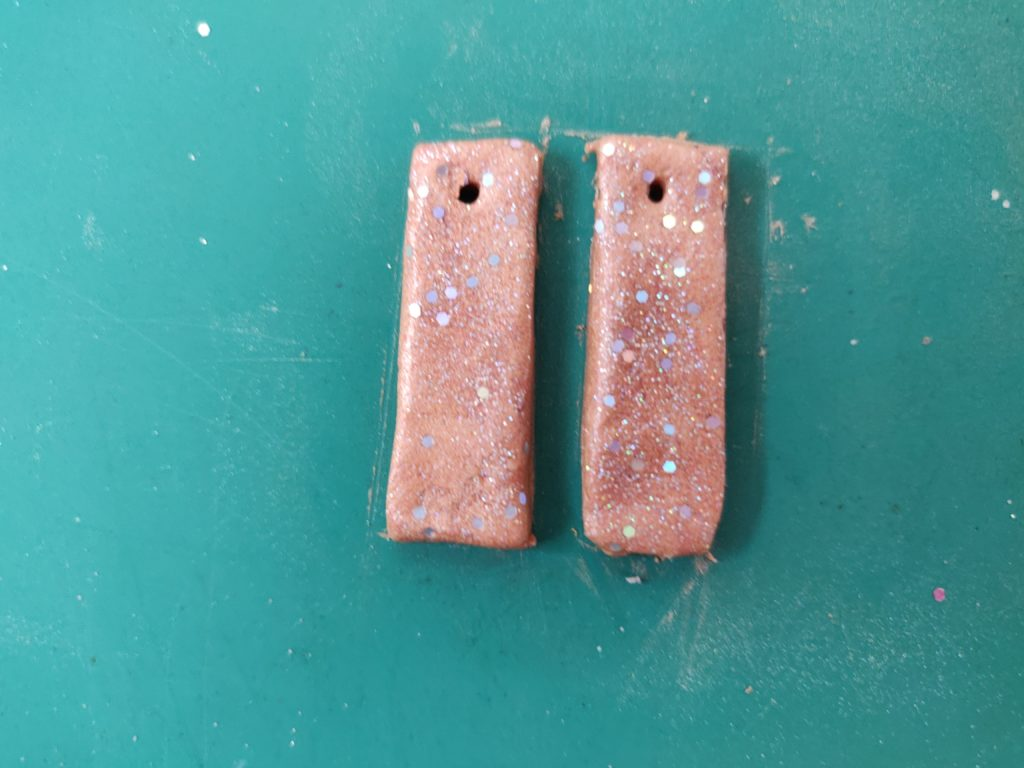 Two finished unbaked clay earrings with a hole in each