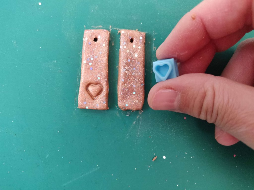 Clay earrings being stamped with heart shaped impression cutter