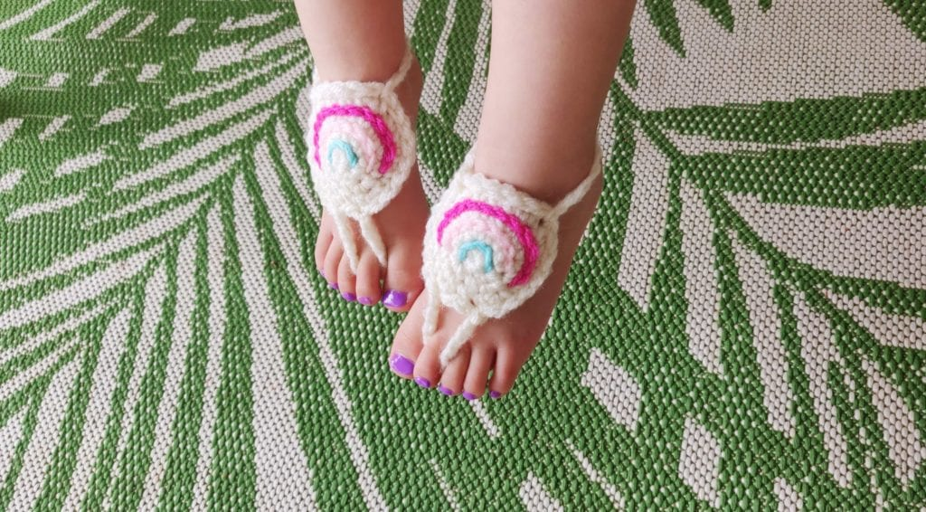 Rainbow barefoot crochet sandals on infants foot with purple nail polish and a leafy green background