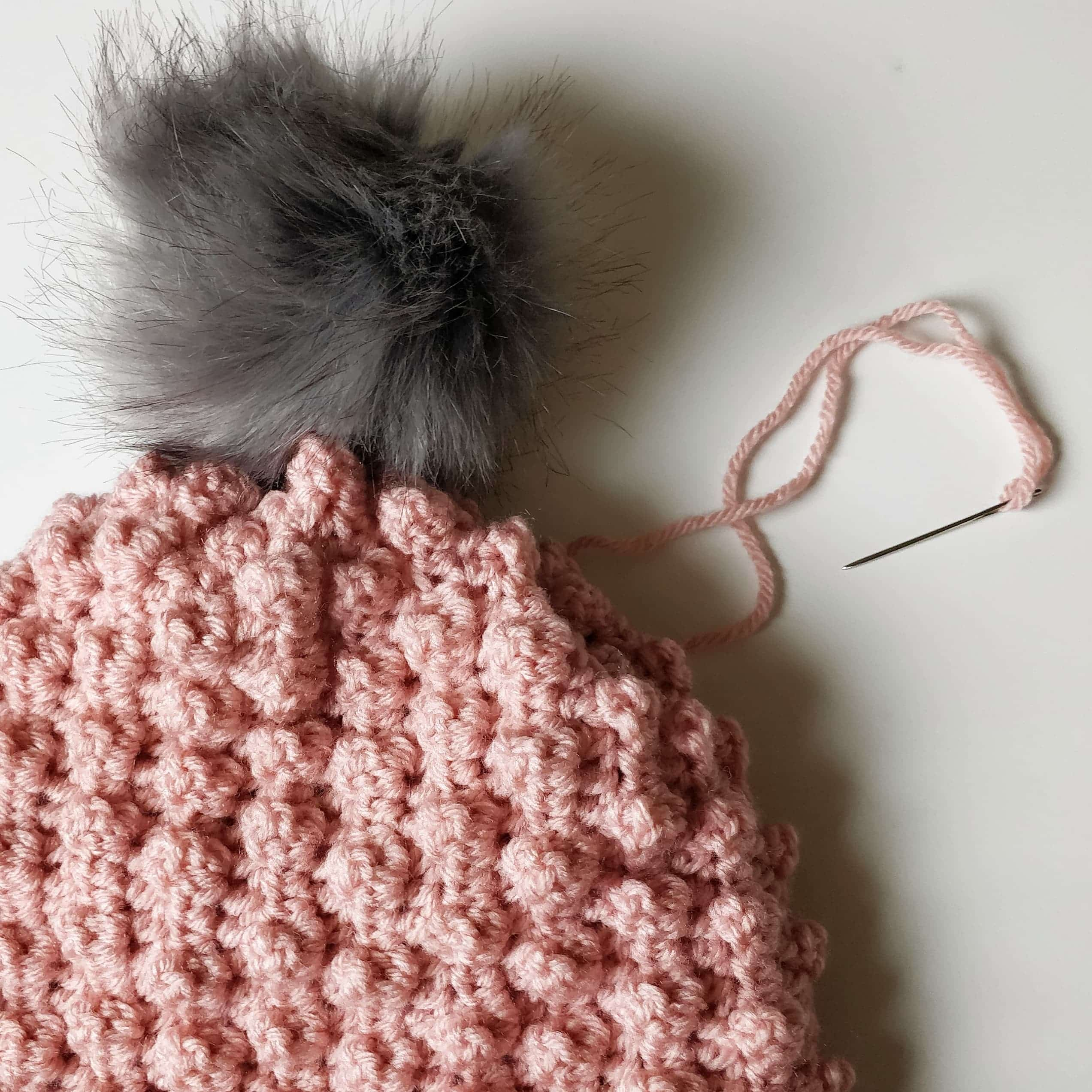Picture shows and pink crochet beanie with a gray faux fur pom pom.