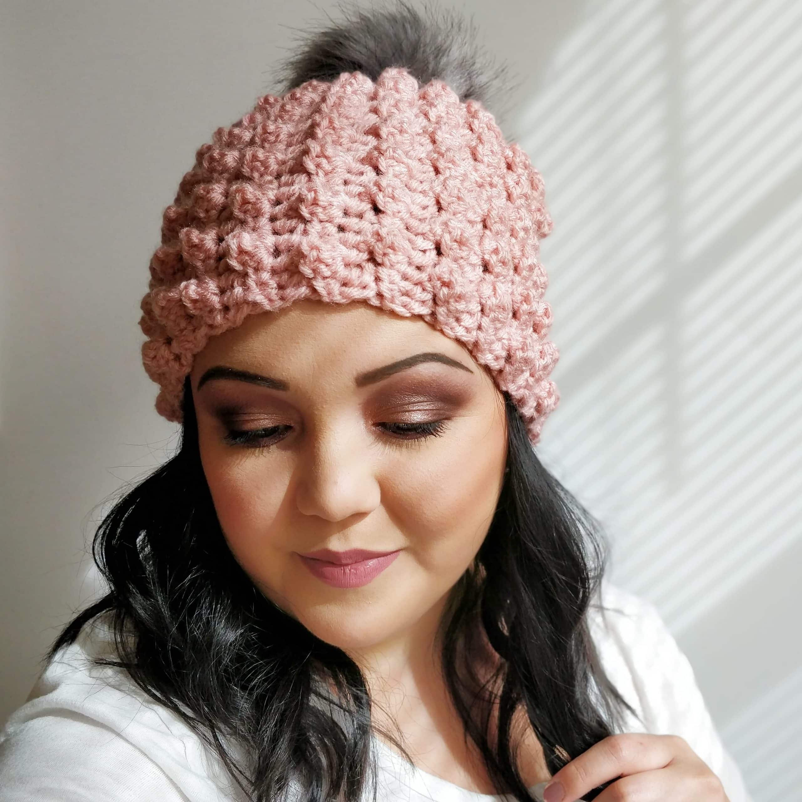 Woman wearing a handmade crochet pink beanie with gray faux fur pom pom.