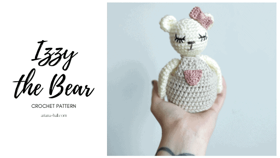 Izzy the bear is crocheted has a taupe dress with pink pocket and bow.