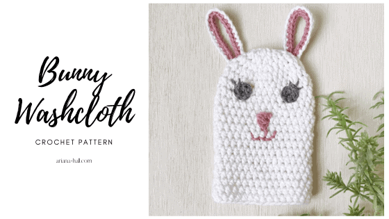 White bunny washcloth with a happy face and ears as loops to hang from.