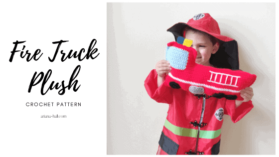 Kid fire fighter holding a crochet fire truck.