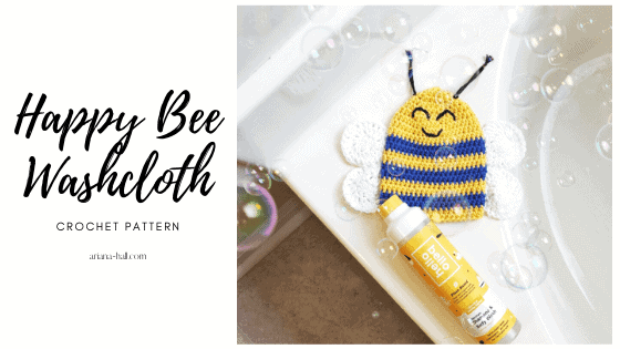 A blue and yellow bee crochet washcloth with white wings and black antennas.