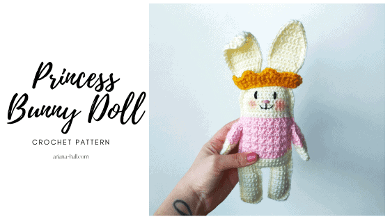 Crochet bunny with textured pink shirt, big floppy ears and a gold crown.