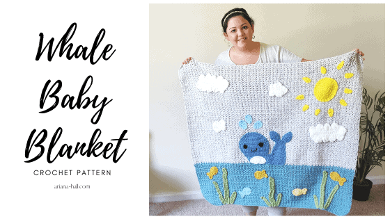 A person holding up a whale themed crochet baby blanket.