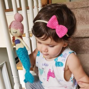 Little girl wearing a pink crochet bow headband and holding a mermaid.