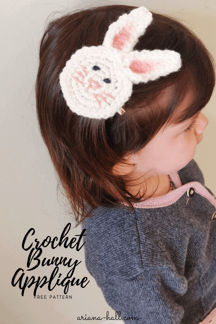 Beautiful 2 year old toddler girl with medium length hair wearing a crochet bunny applique in her hair. She is dressed in a gray and pink sweater.