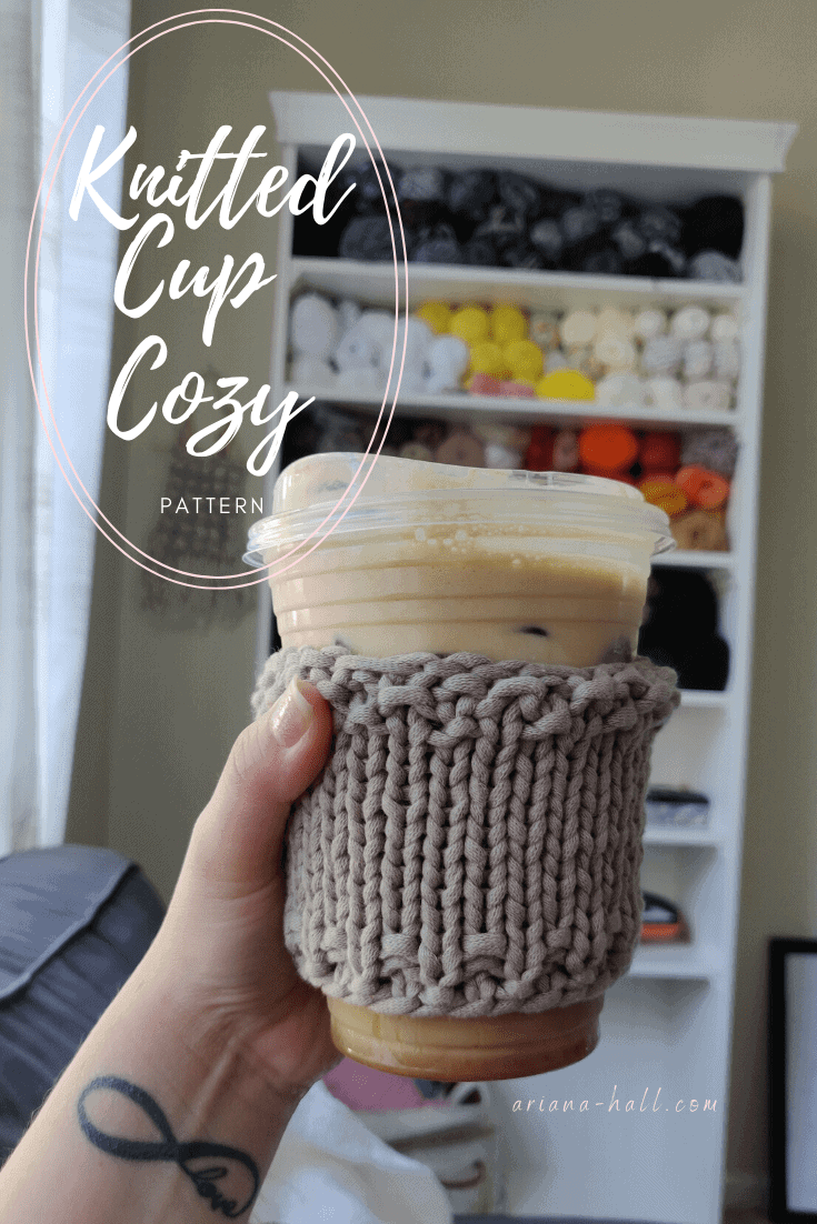 Coffee cup with a taupe knit cup cozy sleeve.