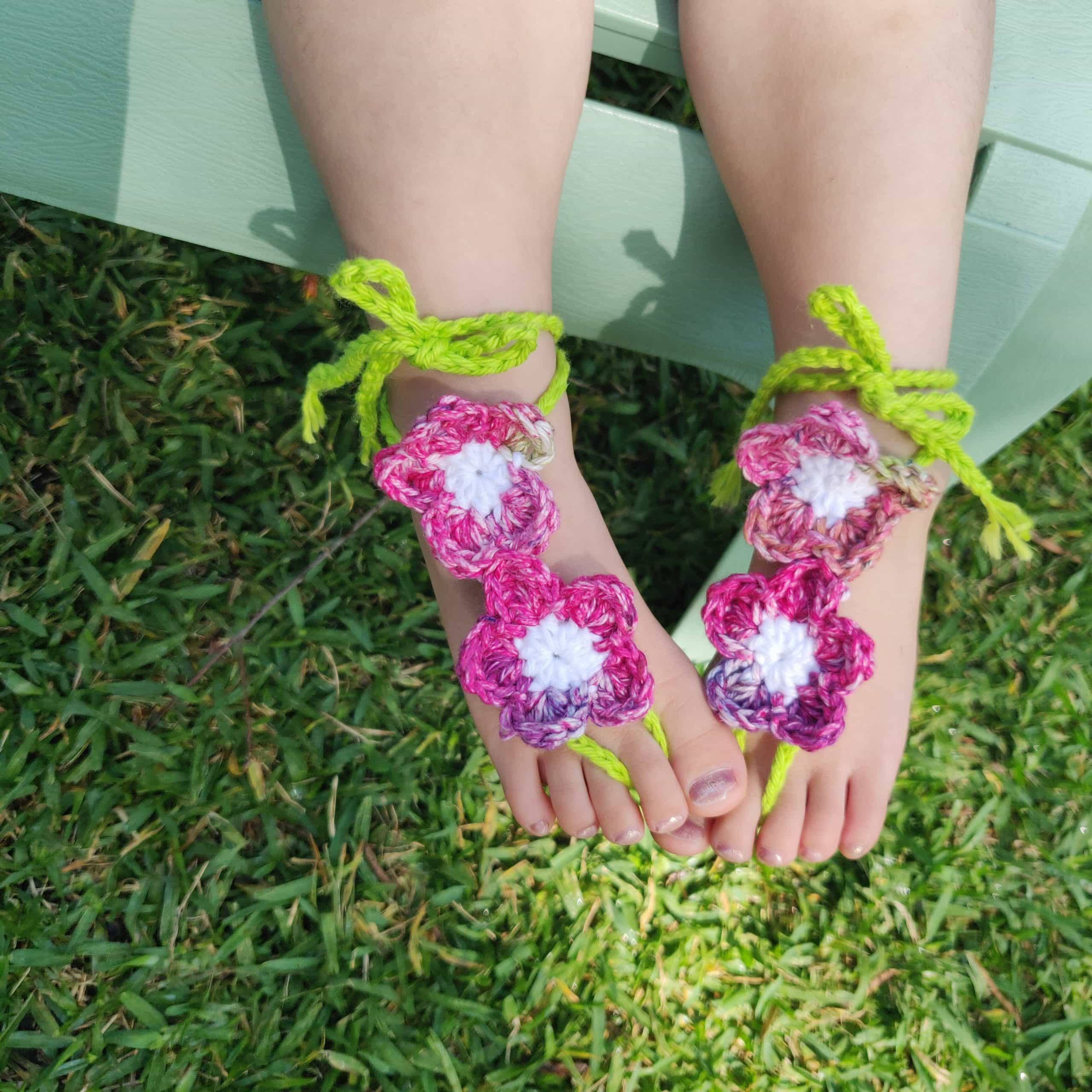 Crochet barefoot sandals made with colorful flowers and tied around the ankle.