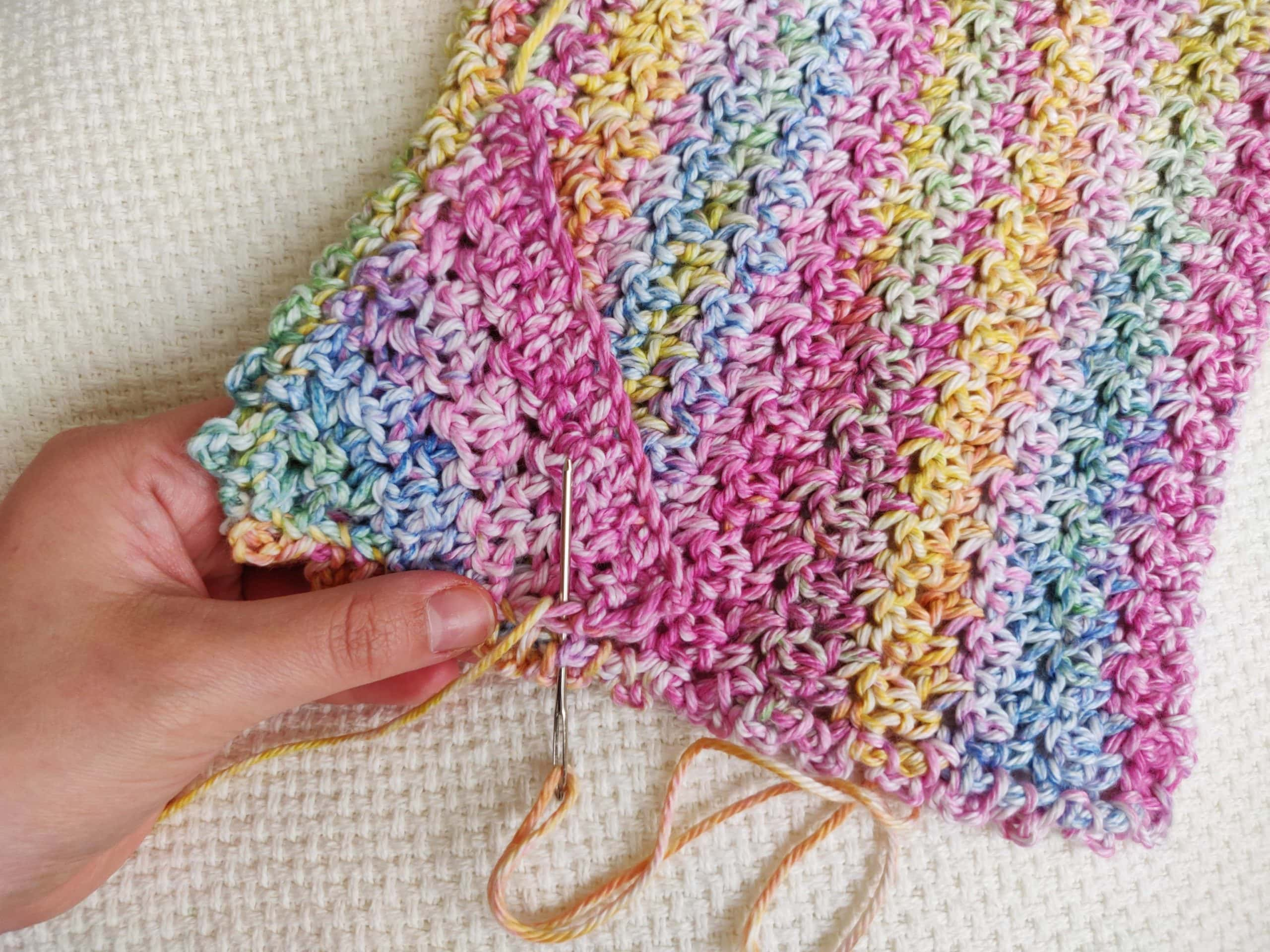 Sewing on a crochet triangle piece to the crochet washcloth corner.