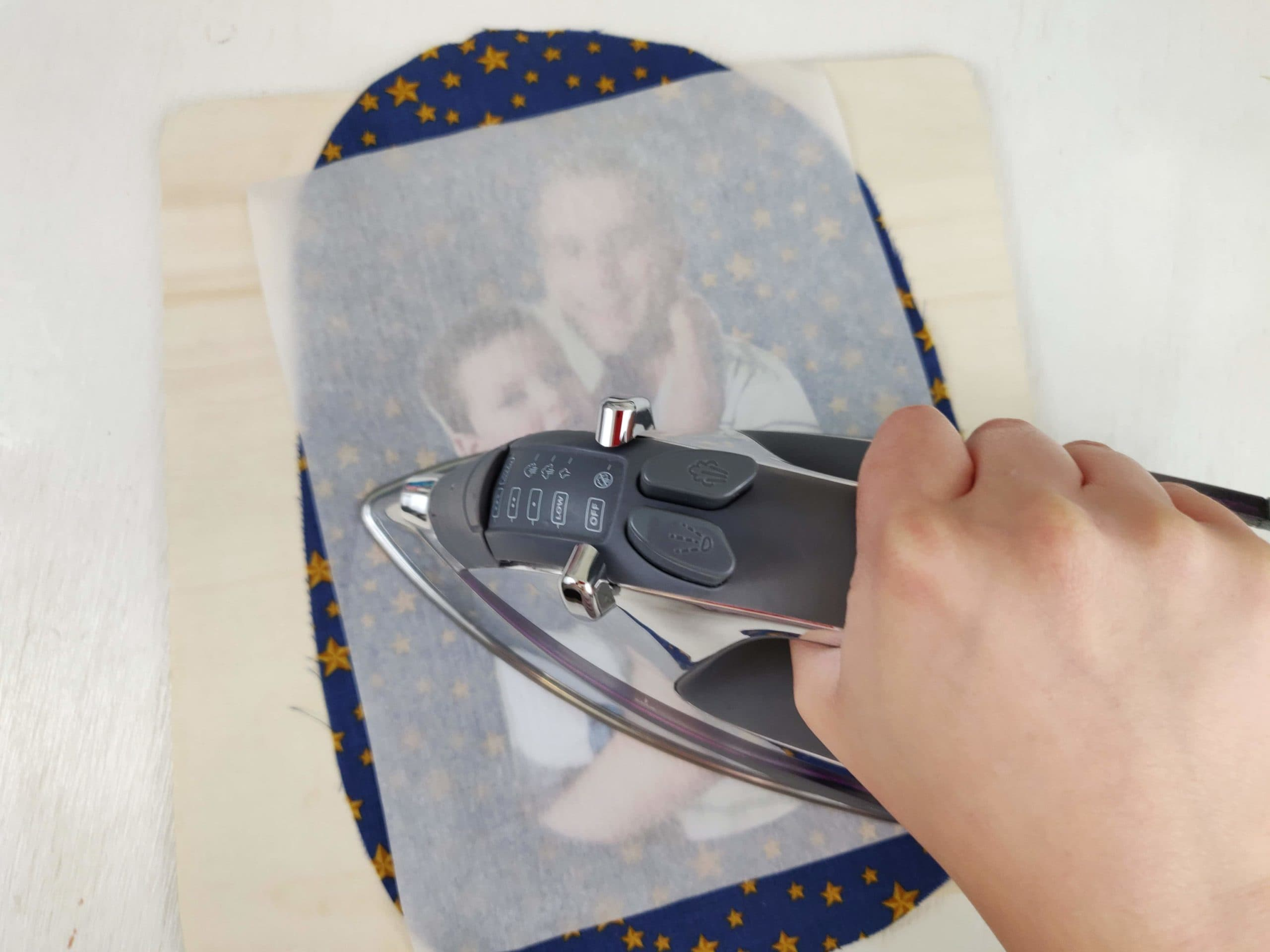 Ironing image using transfer paper on top of cotton fabric.