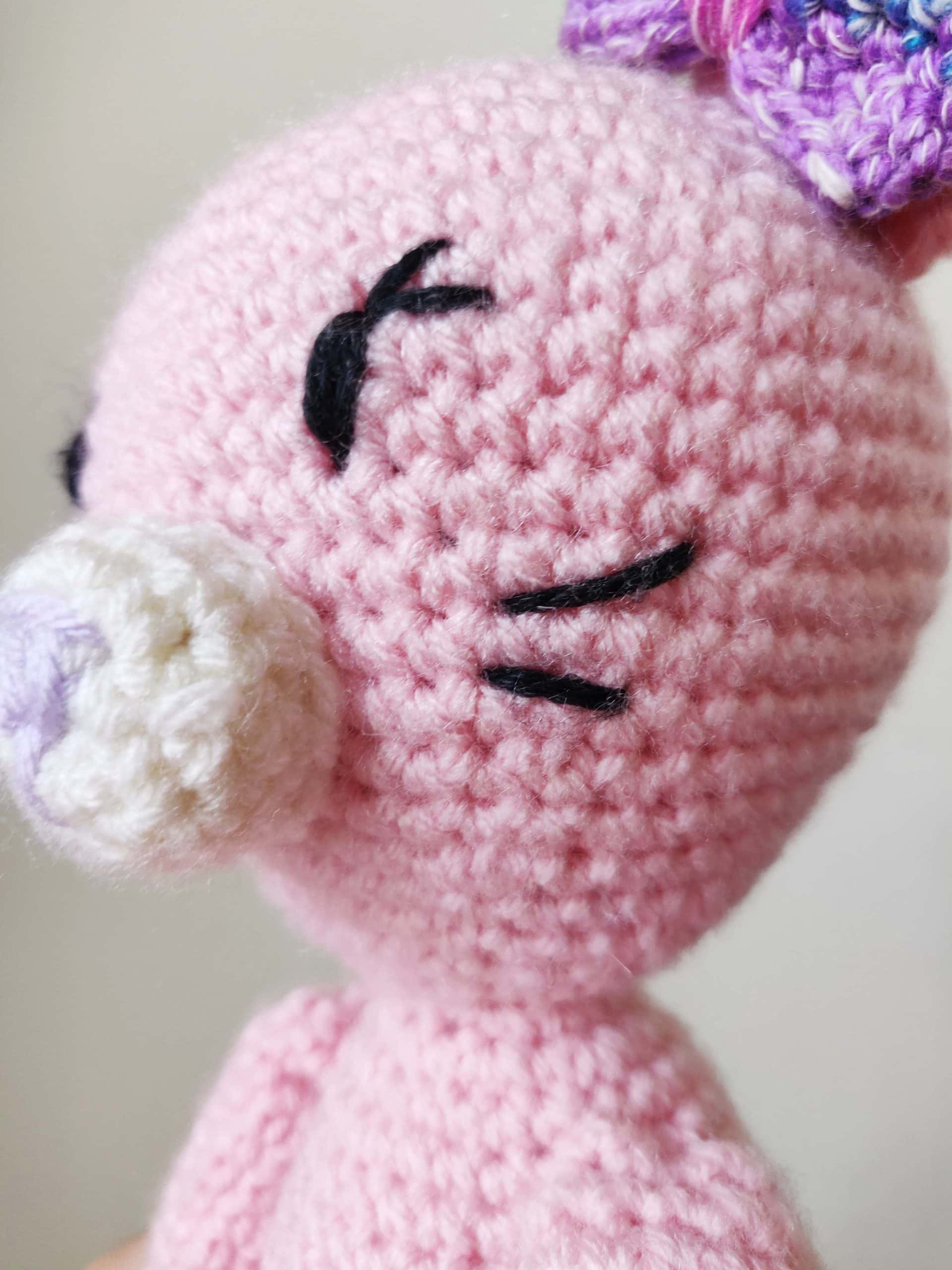 Crochet pink cat with rainbow bow.