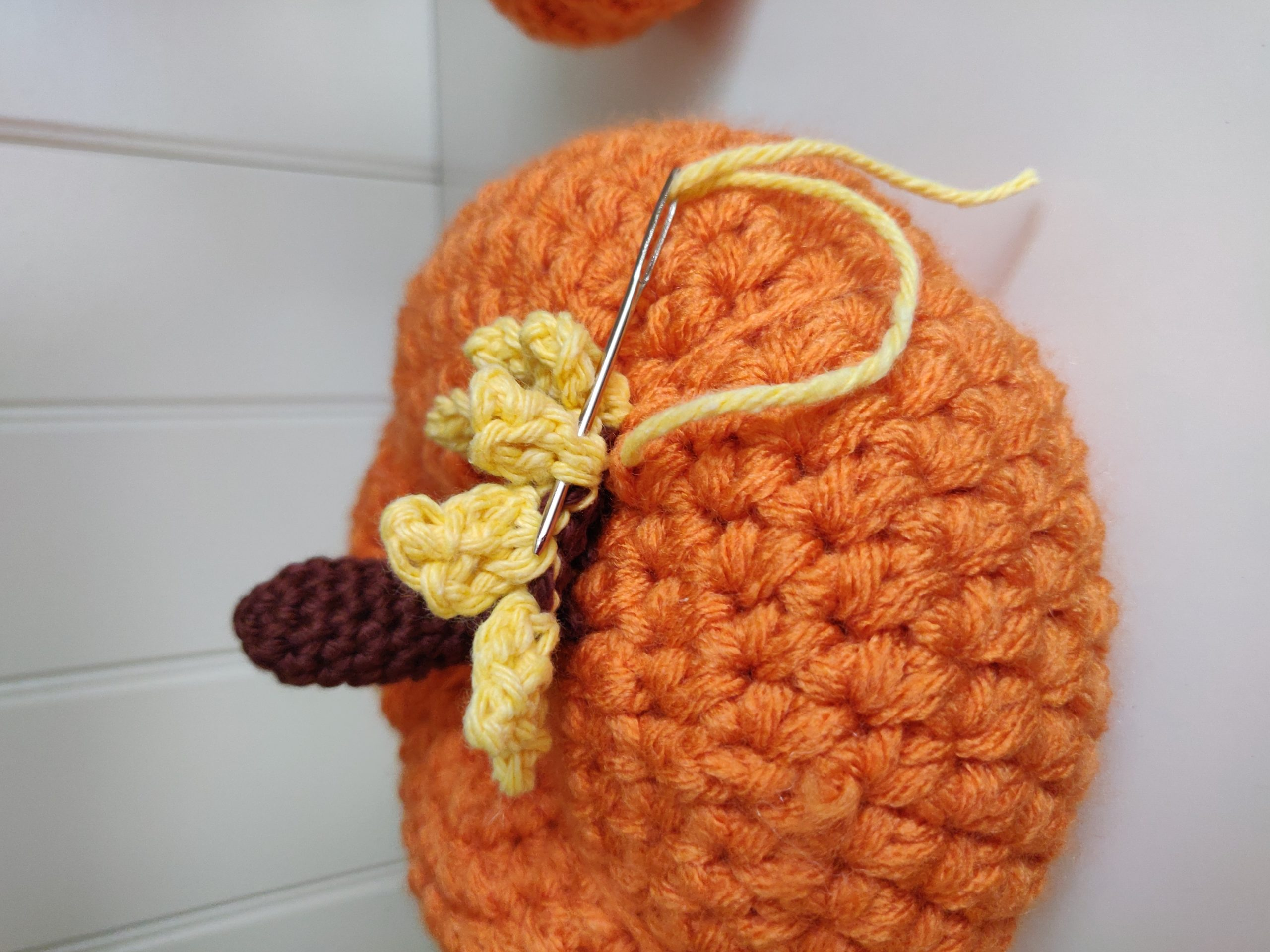Crochet pumpkin with sunflower sewing on the flower on the pumpkin.